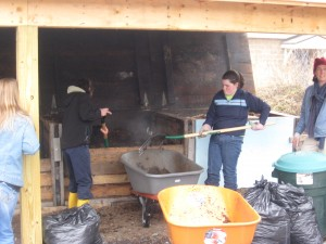 Thetford Elementary student Katie Howard pitches in with Jean Graber and Marty Bouchard to work the compost.