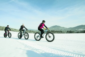 A group of fat bike riders enjoying a winter bike ride on the Kingdom Trails, in East Burke, VT. Photo courtesy of Kingdom Trails, and taken by Herb Swanson.
