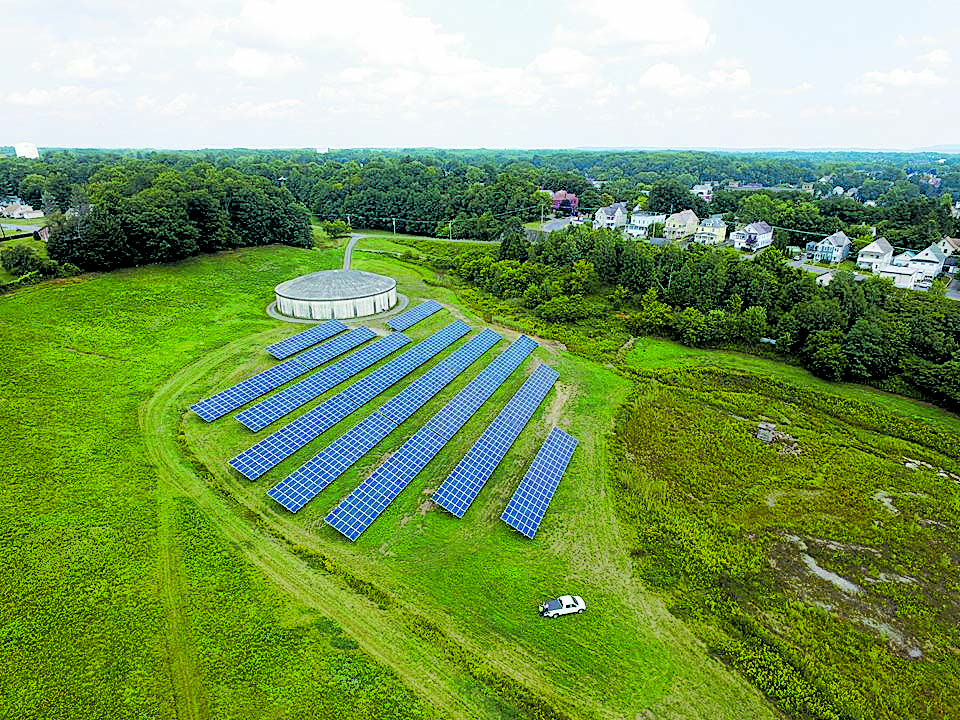 An aerial view of the 2,000 panel solar garden that was built on a decommissioned reservoir in Amsterdam, NY, the panel frames during installation and the undersides of panels where the inverters are located. Photos courtesy of John Hodgens.