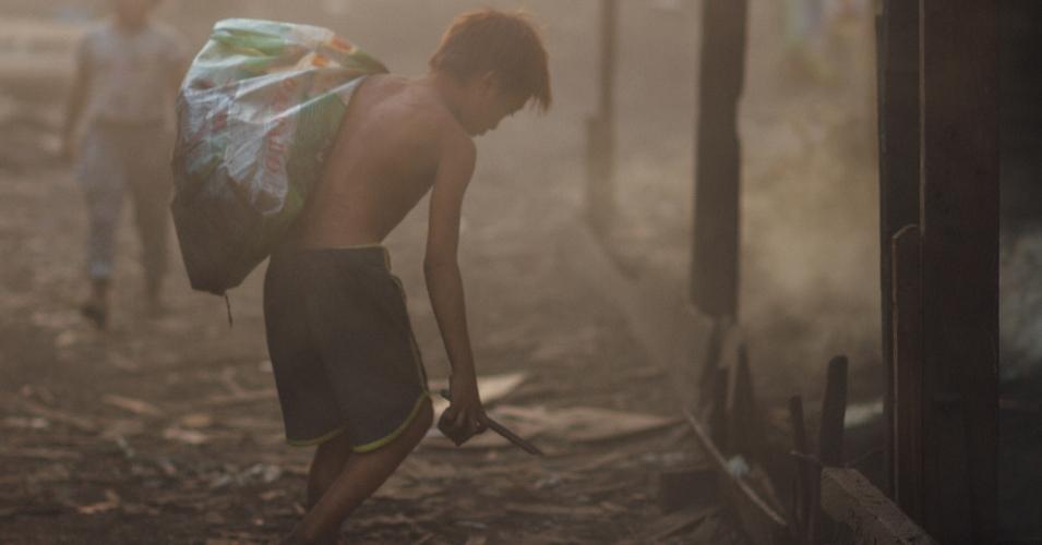 A child scavenges for coal scraps in a slum in Manila. (Photo: Adam Cohn / flickr / cc.)