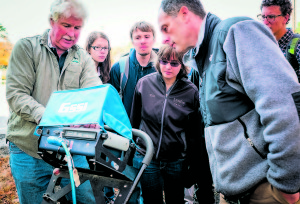 Todd Workman, Executive Director of PermaCityLife, joins students as they observe the utilization of a Geoprobe to identify environmental contaminants in the soil.