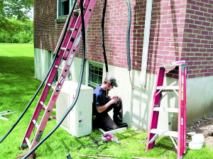 Refrigerant and electrical lines are connected to the outdoor heat pump unit.