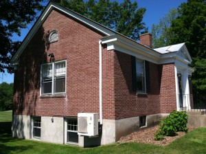 A multi-zone,  Mitsubishi Electric 36,000 BTU heat pump system serves to cool and heat the Meriden, New Hampshire Library. Left: The installed outdoor unit rests on a bracket to keep it above the level where snow can build up. Line-hide enclosure covers the refrigerant, condensate and control lines running up the side of the building.