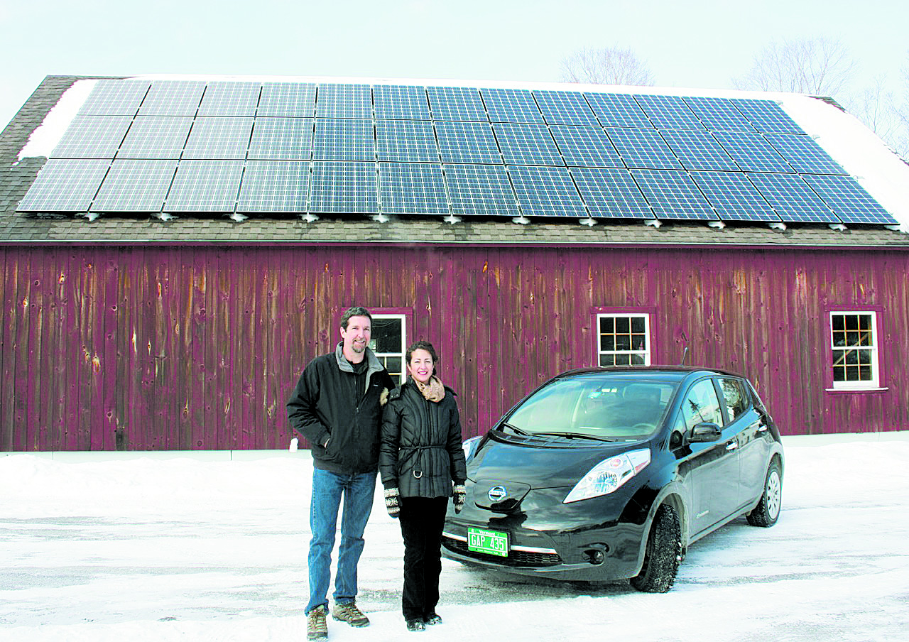 Bill and Lisa Laberge with their electric car in front of their barn with a 9.5kW solar array. Courtesy photo.