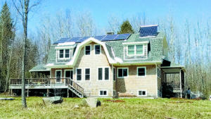 A 5.13kW solar PV array using U.S.-made Solarworld modules was added to the home of an Ammonoosuc Regional Energy Team member. This home was previously outfitted with a solar hot water collector. Photo courtesy of O'Meara Solar.