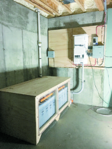 24 volt NiFe Iron Edison battery bank encased in a vented, birch plywood box with a plexiglass front to monitor the electrolyte levels. Mounted on the wall is a Magnum 4400 Watt inverter.