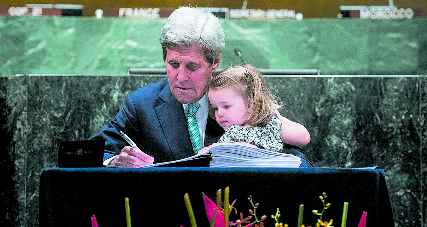 United States Secretary of State John Kerry signed the Paris Agreement on April 22, 2016 with his granddaughter in his arms. Photo: UN Photo/Amanda Voisard/CC BY-ND (Flickr)