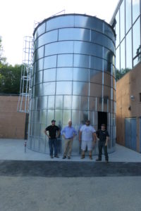The Froling Energy crew stands by the new 42 ton wood chip silo which is 19 feet in diameter and 30 feet high.