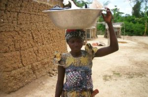 African village girl with baby, laundry and dishes.