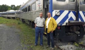 In this Sept. 5, 2017 photo, David Blittersdorf, right, and Charlie Moore pose in Barre, Vt., in front of one of a dozen passenger rail cars Blittersdorf bought to try to jump-start a commuter rail system in Vermont. Moore, a long-time rail expert in the state, is working to make that happen.