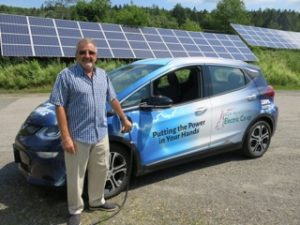 With the panels of his solar PV array in the background, Guy LaPerle, owner of LaPerle's IGA in Colebrook, marked the opening of New Hampshire's northernmost public charging station by topping off NHEC's all-electric Chevrolet Bolt.