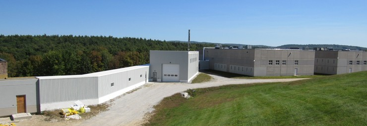 The currently occupied Merrimack County prison at right is tied into the new biomass boiler building and the second prison (not seen to left) through a long enclosed corridor that also contains the heat pipes from the boiler.