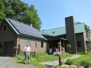 Bill Sullivan in front of solar panels installed during a solarize initiative
