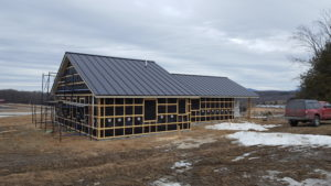 The Floersch home in Berlin, VT with solar PV field in the background at the right. Credit: Larry Floersch.