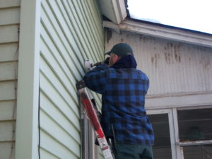 David Mack, Weatherization Crew Technician, drills a hole for the installation of a bathroom ventilation fan, which helps prevent mold in a weatherized home.