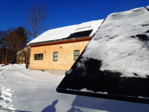 Tin Mountain's main building with built in PV's (left portion of roof) begins to shed snow when the ground mount s