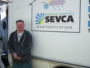Harald O'Brien, Weatherization Crew Chief, stands next to one of SEVCA's weatherization trucks, parked on-site at a home in Brattleboro. Courtesy images: Becky Himlin, SEVCA